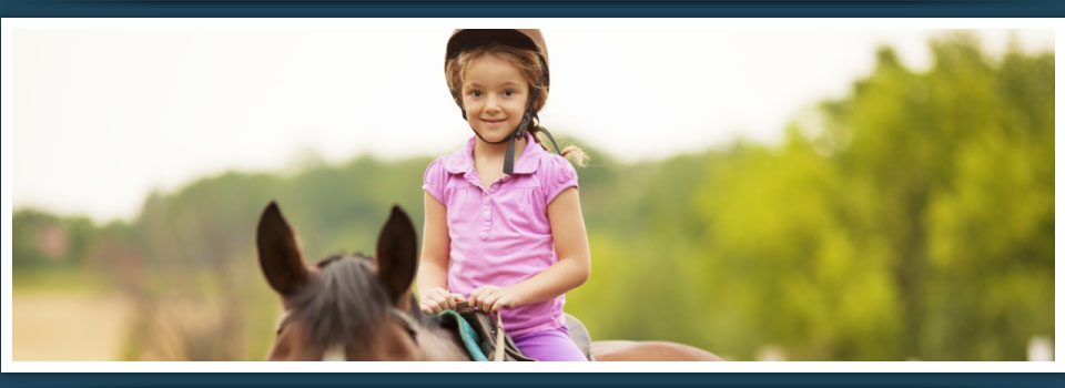 Young girl riding horse at summer camp